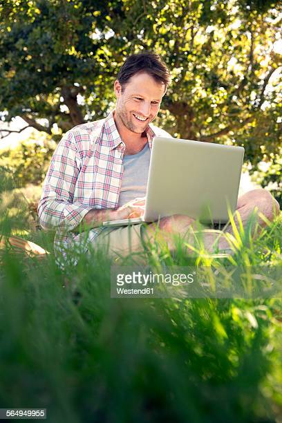 Smiling man with laptop sitting on meadow