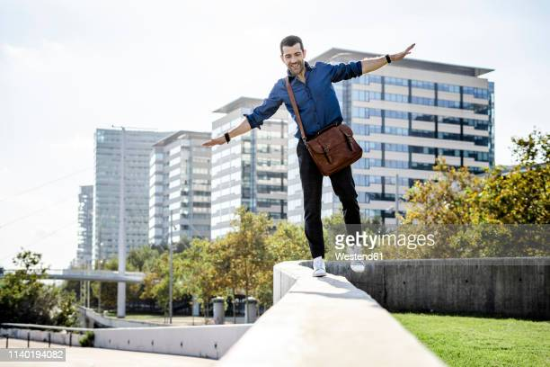 smiling man with leather bag balancing on wall - standing on one leg stock pictures, royalty-free photos & images