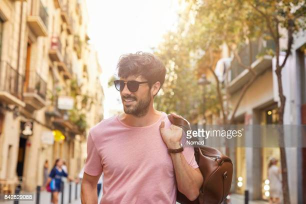 Smiling man with leather bag walking on street