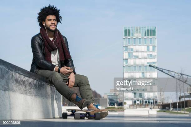 smiling man with longboard sitting in skatepark listening to music on his smartphone - black jacket stock pictures, royalty-free photos & images