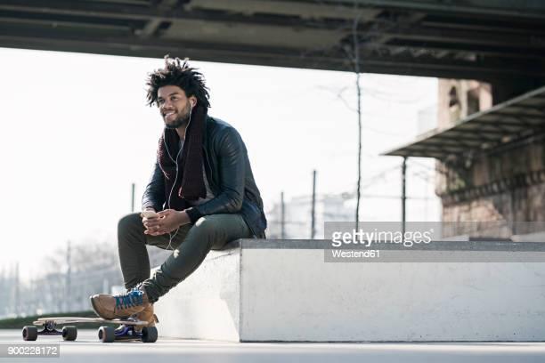 smiling man with longboard sitting in skatepark under bridge holding a smartphone - longboard skating stock-fotos und bilder