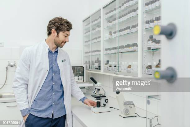 Smiling man with microscope in laboratory