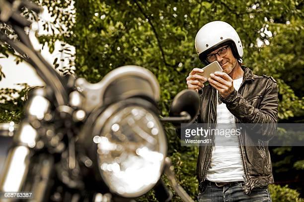 Smiling man with motorcycle helmet taking photo of his motorbike