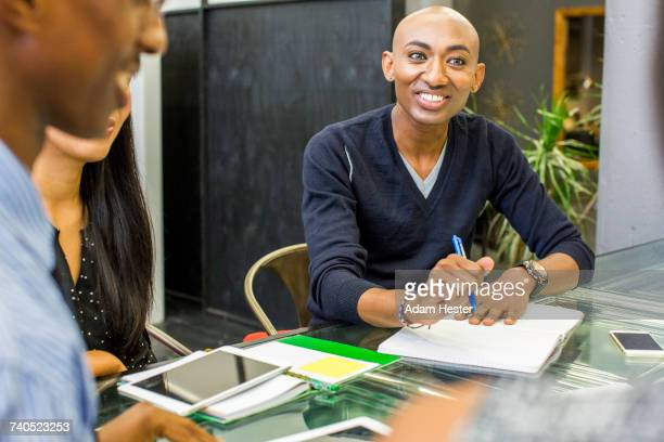 smiling man with notebook in meeting - non binary gender stock pictures, royalty-free photos & images