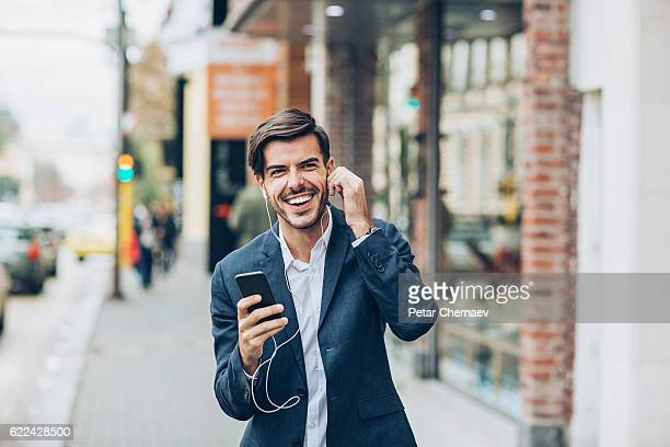 Smiling man with phone and headphones on the street