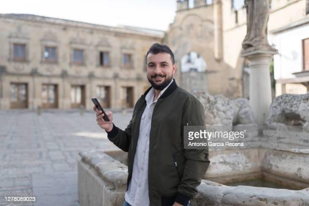 """smiling man with phone in """"plaza del populo""""u201d baeza, spain. - zwart haar stockfoto's en -beelden"""