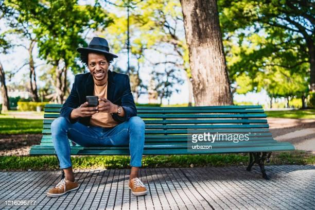 uomo sorridente con telefono in panchina - panchina foto e immagini stock