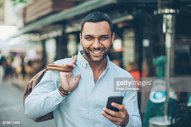 Smiling man with phone on the street