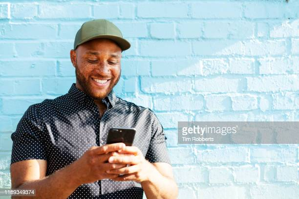 smiling man with smart phone - millennial generation stock pictures, royalty-free photos & images