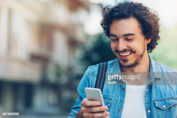 smiling man with smart phone - text stock pictures, royalty-free photos & images