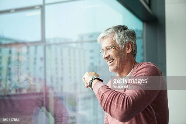 Smiling man with smartwatch looking through window