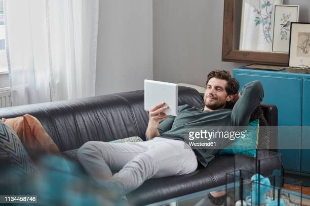 smiling man with tablet lying on couch at home - sofa stock-fotos und bilder