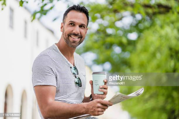 smiling man with takeaway coffee and newspaper in a park - striped shirt stock pictures, royalty-free photos & images