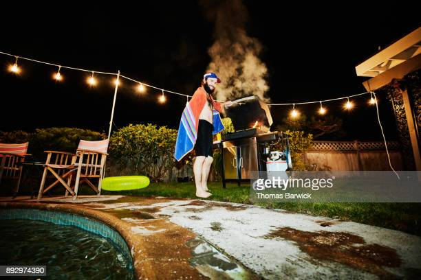 Smiling man with towel around shoulders grilling food on barbecue during party on summer evening