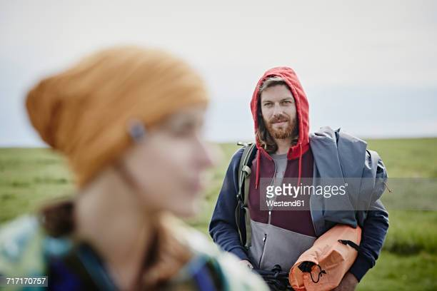 Smiling man with woman in foreground on a trip