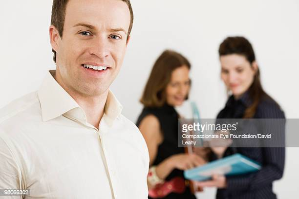 smiling man with women in background