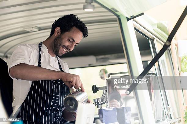 Smiling man working in a food truck