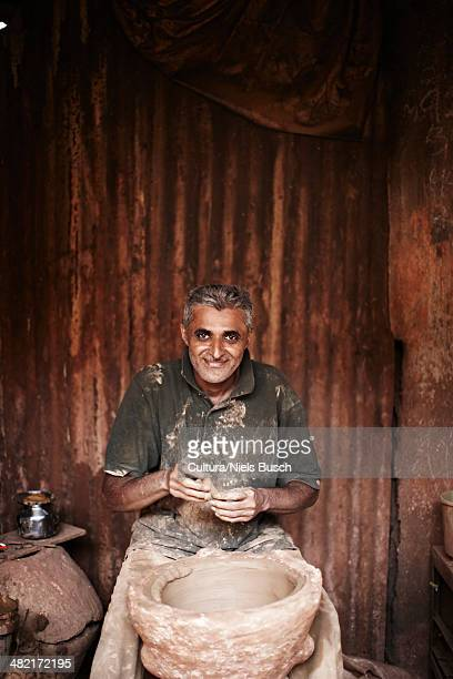 Smiling man working with pottery