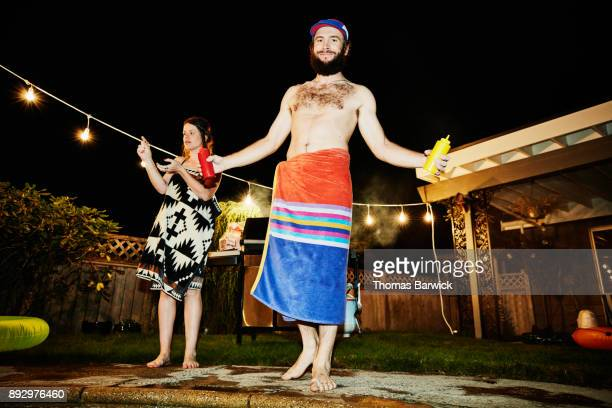 Smiling man wrapped in towel holding ketchup and mustard while grilling for friends in backyard during party on summer evening