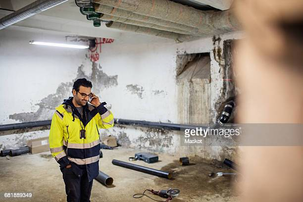 Smiling manual worker talking on phone in basement