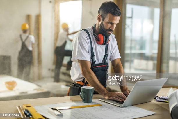 smiling manual worker using a computer at construction site. - building contractor stock pictures, royalty-free photos & images