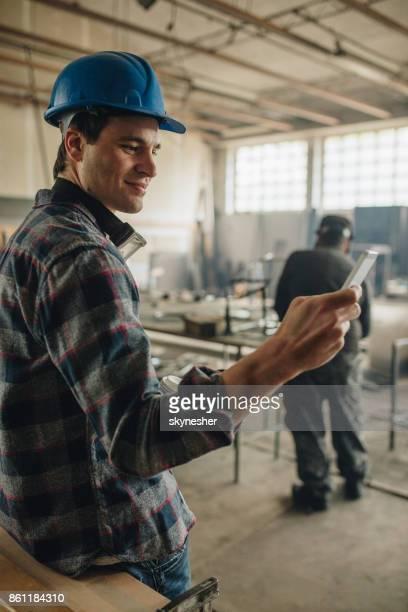 Lächelnde Arbeiter mit Smartphone in einer Werkstatt.