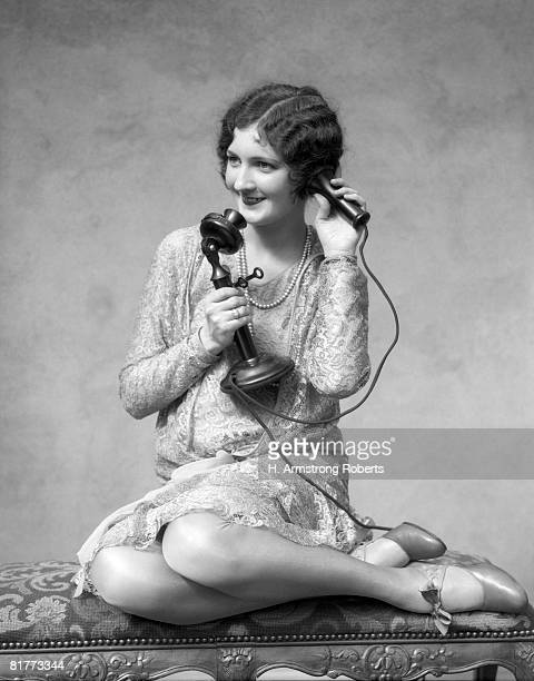 Smiling Marcel Waved Woman Talking On The Telephone While Reposing On The Divan With Her Legs Crossed Wearing A Silk & Lace 2 Piece Dress Mary Jane Pump.