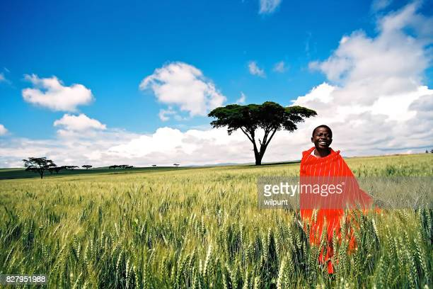 A smiling Masai boy standing in wheat field