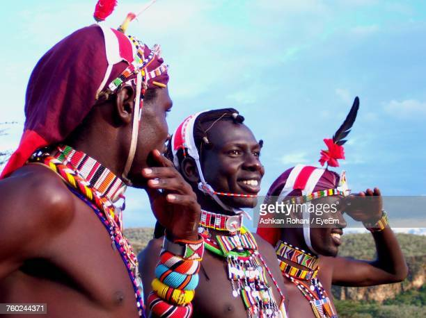 Smiling Masai Men Wearing Traditional Clothing Against Blue Sky