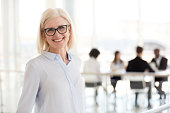 Smiling mature attractive businesswoman in glasses looking in camera