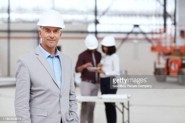 smiling mature building engineer with colleagues working in the background - real estate developer stock pictures, royalty-free photos & images