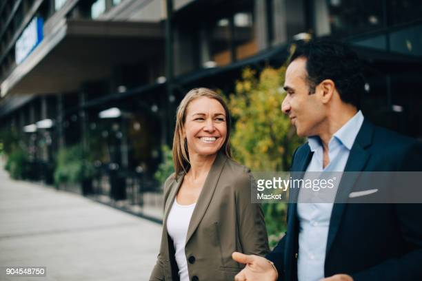 smiling mature business colleagues talking while walking in city - businesswear stock pictures, royalty-free photos & images