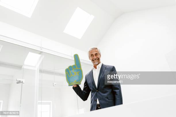 smiling mature businessman holding toy hand in office - concepts & topics stock pictures, royalty-free photos & images