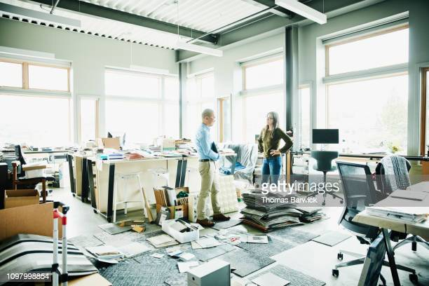 smiling mature businessman in discussion with coworker in design studio - imperfection stock pictures, royalty-free photos & images