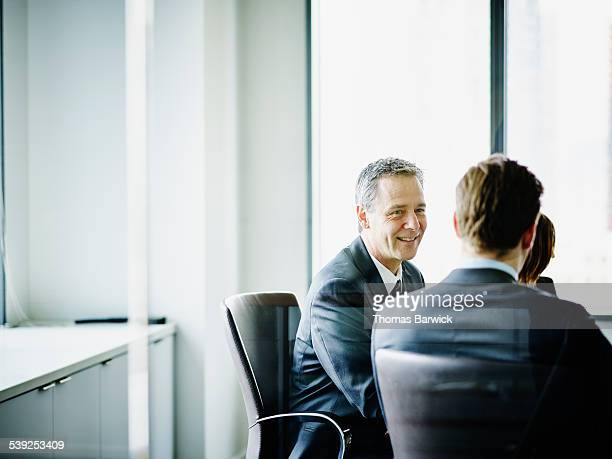 Smiling mature businessman leading team discussion