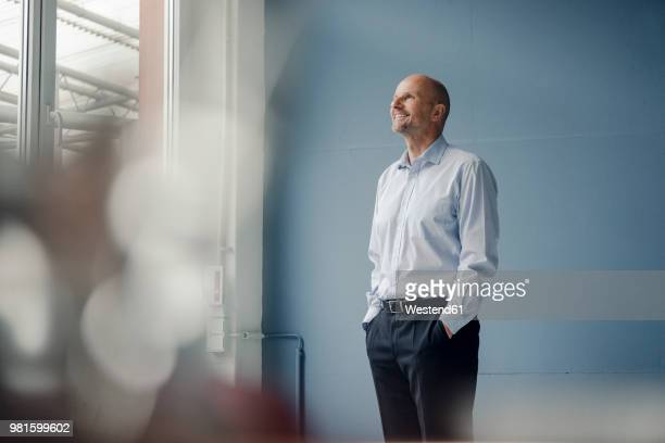 smiling mature businessman looking out of window - dreiviertelansicht stock-fotos und bilder