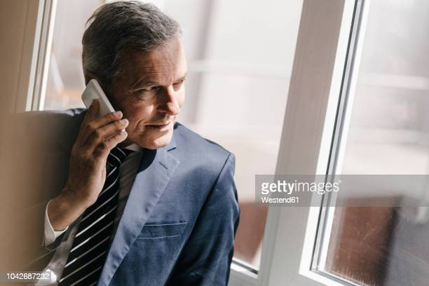 smiling mature businessman on cell phone looking out of window - 陰謀 ストックフォトと画像