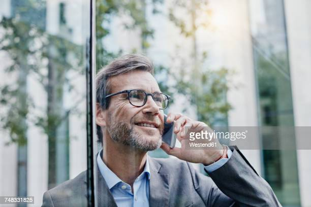 Smiling mature businessman on cell phone