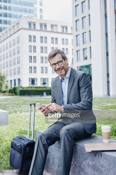 Smiling mature businessman outdoors with laptop, cell phone, takeaway coffee and rolling suitcase