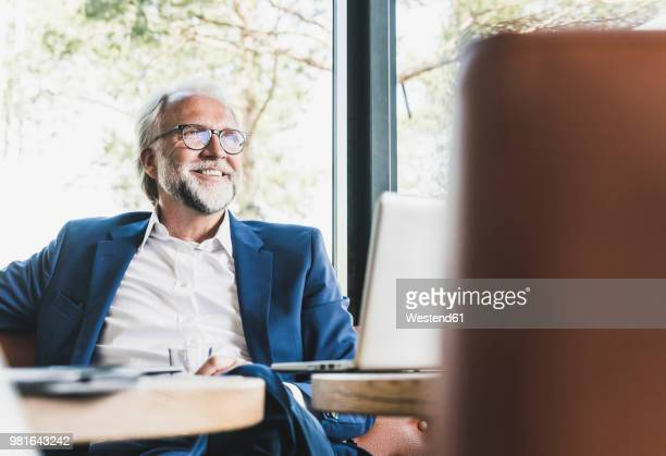 smiling mature businessman sitting at table in a cafe with laptop - geschäftsmann stock-fotos und bilder