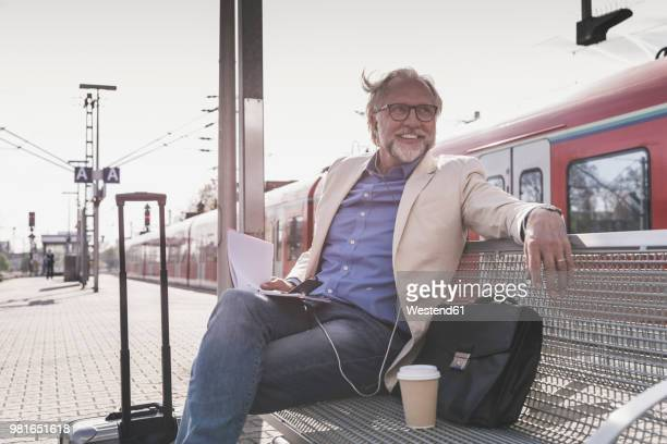 smiling mature businessman sitting at train station with cell phone, earbuds and notebook - railroad station stock pictures, royalty-free photos & images