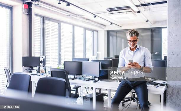 Smiling mature businessman sitting on desk in office using smartphone