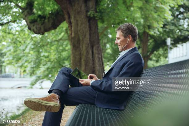 smiling mature businessman sitting on park bench with tablet and earphones - sitzen stock-fotos und bilder