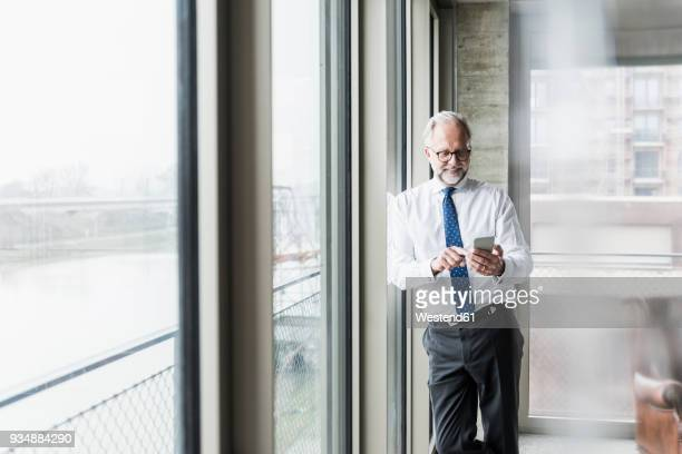 Smiling mature businessman standing at the window using cell phone