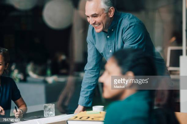 Smiling mature businessman standing by female colleagues in board room during meeting