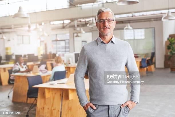 homem de negócios maduro de sorriso que está em um grande escritório moderno - mãos no bolso - fotografias e filmes do acervo