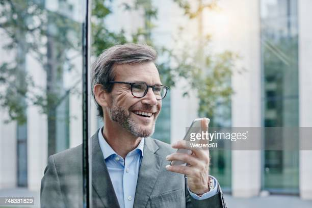 Smiling mature businessman using cell phone