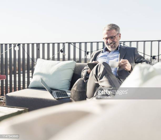 smiling mature businessman using tablet on roof terrace - geschäftskleidung stock-fotos und bilder