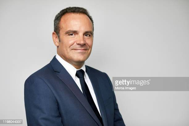 smiling mature businessman with arms crossed - suit stock pictures, royalty-free photos & images