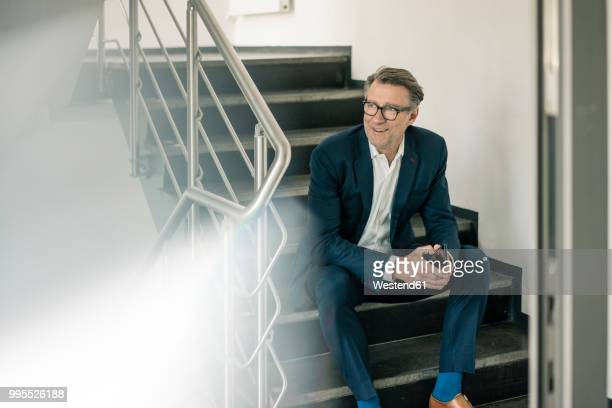 Smiling mature businessman with cell phone sitting on stairs